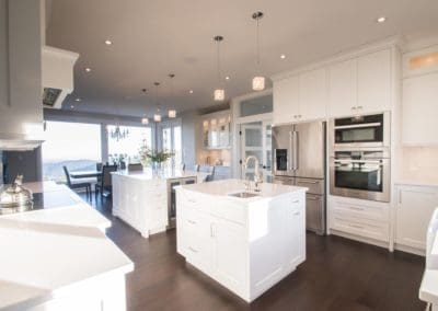 Complete view of kitchen area with two islands and double ovens in custom home