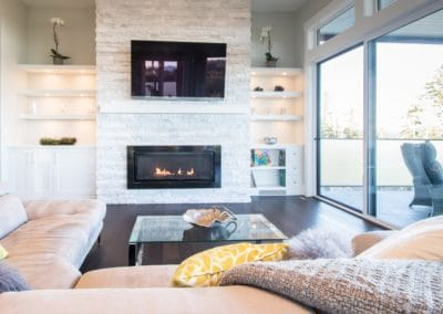 Living area with relaxing fireplace and TV in goldstream heights custom home
