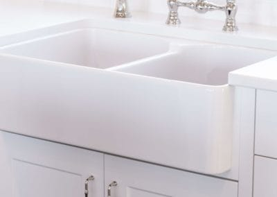 White farmhouse sink with chrome fixtures in goldstream heights custom home