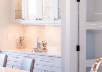 White and glass cabinetry in kitchen of custom built home