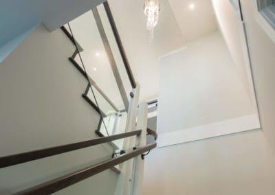 Looking up at stairs in custom built home, chandelier in ceiling