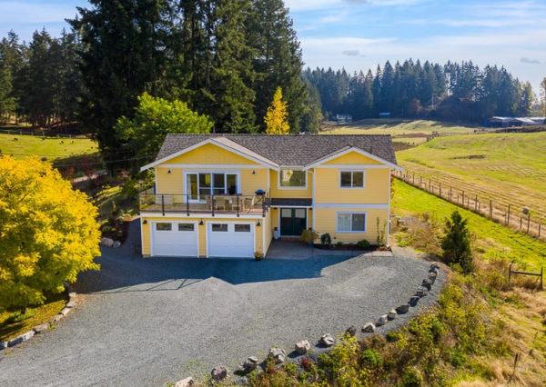 Farmhouse exterior yellow with countryside surrounding