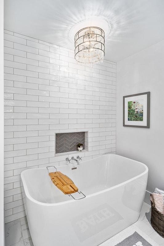 Freestanding soaker tub with subway tile backsplash