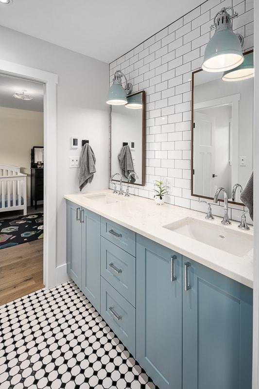 Blue modern farmhouse vanity and black and white tiled floor in bathroom